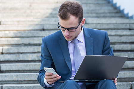 Businessman working on Laptop and iPhone