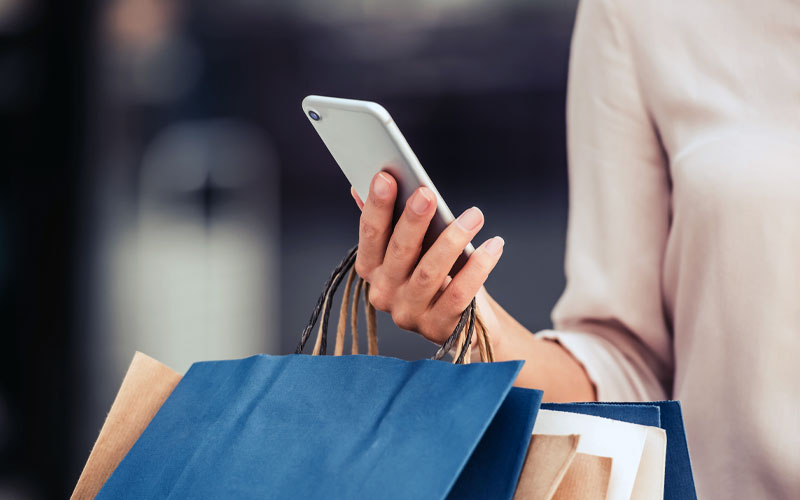 Holding mobile device in hand with shopping bags
