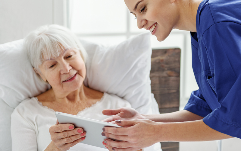 Nurse showing patient how to use personal health assistant on tablet