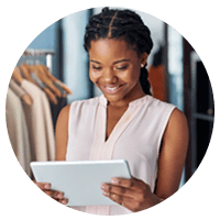 Young businesswoman views solutions on tablet device in clothing store