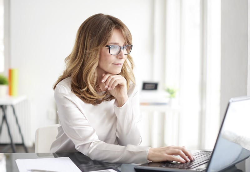 Female business professional using laptop computer in office