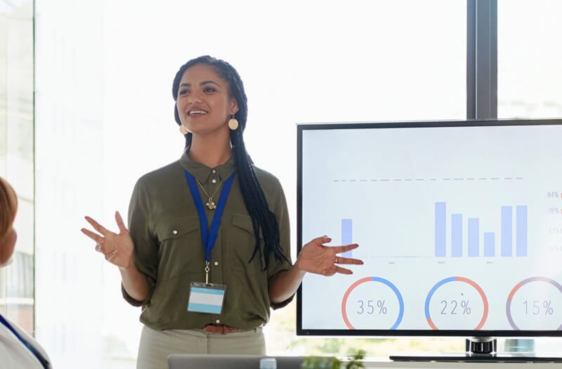 Business woman presenting in front of large flat panel monitor