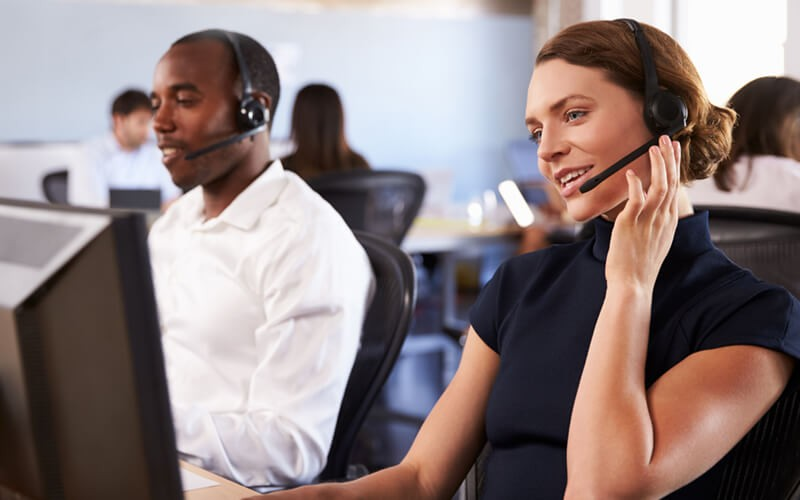 Two call center representatives on headsets
